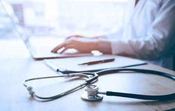 Médico mexendo nas redes sociais pelo computador
